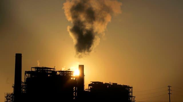 Eine Fabrik mit Rauch vor der untegehenden Sonne.