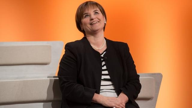 Marina Carobbio sitzt vor orangem Hintergrund, sie lacht.