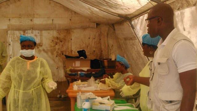 Ärzte an einem Tisch mit Medikamenten in einem Zelt.