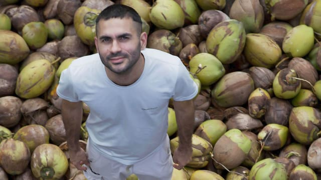 Gabriel Mascaro in weisser Kleidung auf einem Berg von Kokosnüssen.