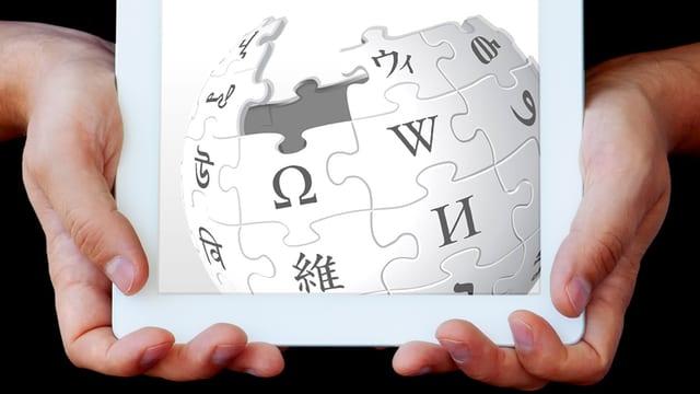 Jemand hält ein Tablet. Auf dem Tablet ist ein Wikipedia-Logo.