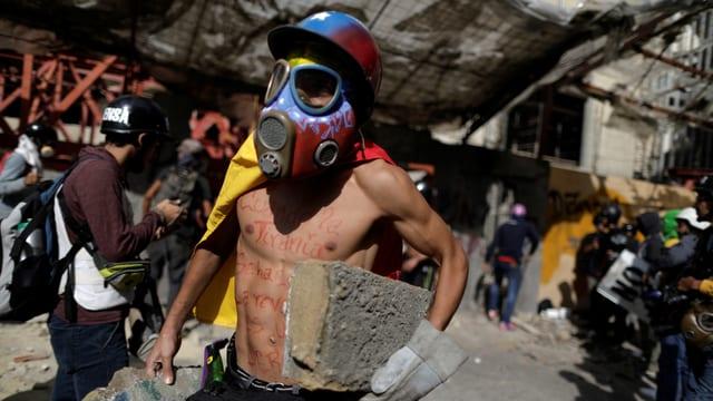 Mit Gasmaske vermummter Demonstrant transportiert Steine.
