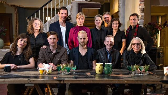 Protagonisten sitzen am Tisch und schauen in die Kamera