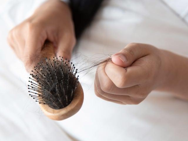 Jemand zieht Haare aus einer Bürste.