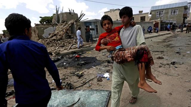Ein Mann trägt einen Jungen, der von der Bombe verletzt wurde.