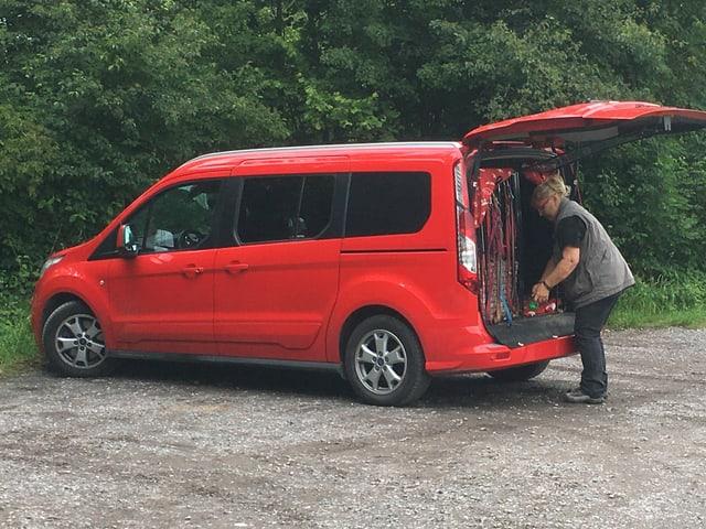 Eine Frau steht bei einem roten Auto beim Hundezwinger.
