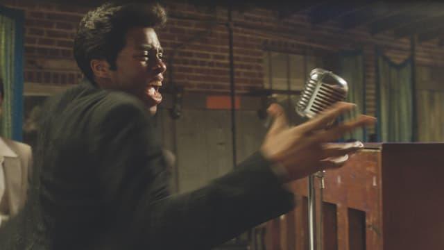James Brown steht am Mikrophon und performt energisch.