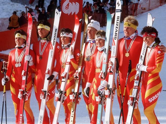 Gruppenfoto mit den erfolgreichen Skirennfahrerinnen und -fahrern. Sie tragen rot-gelbe Renndress und halten ihre Skier in der Hand.