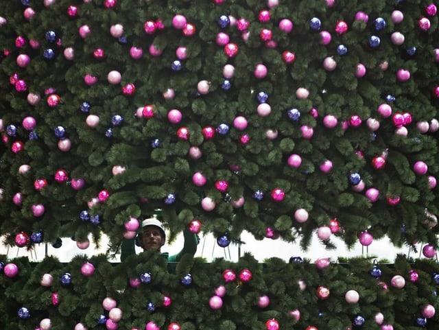 Blick durch einen grossen Weihnachtsbaum in Berlin mit vielen bunten Kugeln auf einen Mann, der die Kugeln aufhängt