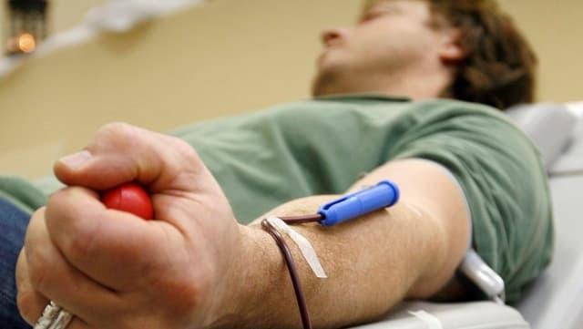 Ein Mann liegt auf einer Pritsche und spendet Blut. Er hat eine Nadel im Arm und einen Gummiball in der Hand.