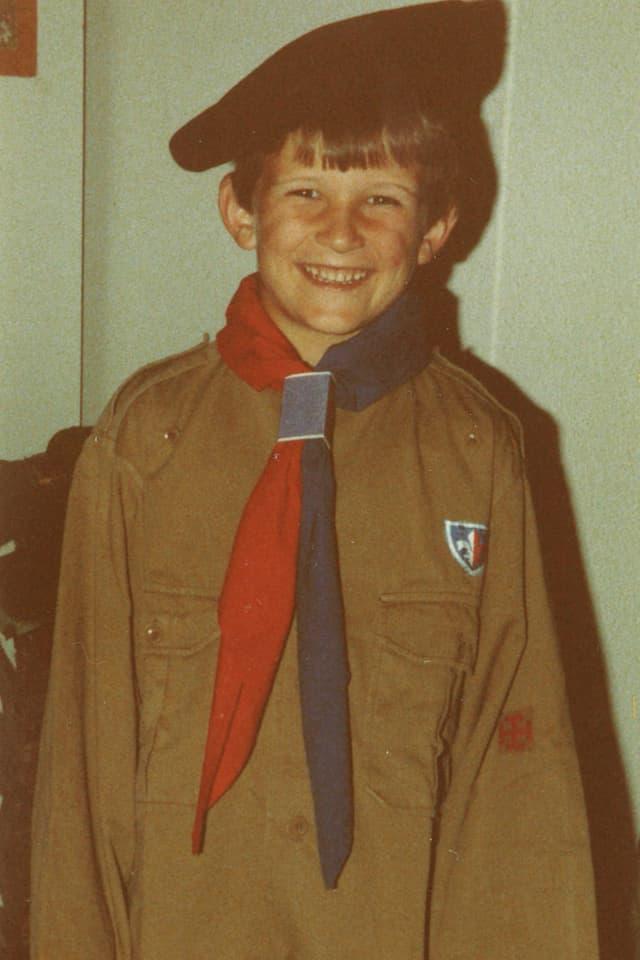 Ein dunkelhaariger Bub trägt ein braunes Hemd und ein rot-blaues Tuch um den Hals.
