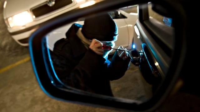 Ein Mann versucht, ein Auto aufzubrechen (Symbolbild).