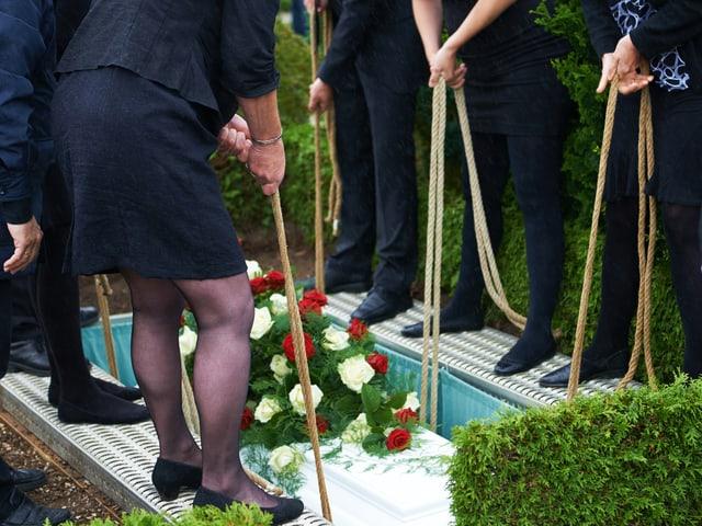 Füsse neben Grab, Hände lassen Sarg hinunter
