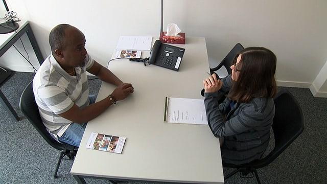 Asylsuchender beim Interview an einem Tisch mit einer Beamtin.
