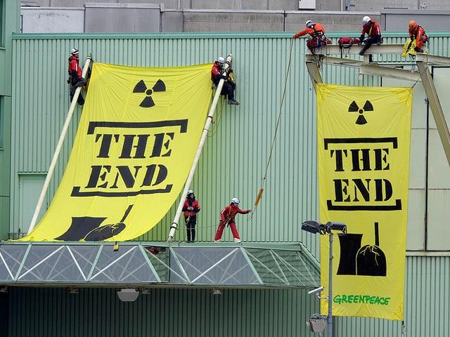 Aktivisten mit Transparenten angeseilt an Gebäude