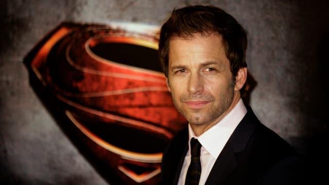 Das Bild zeigt den Regisseur Zack Snyder vor dem Superman-Logo.