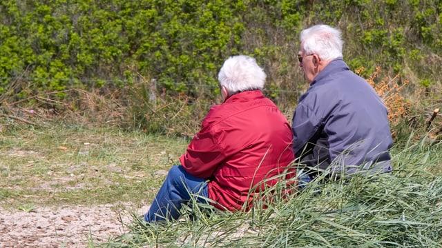 Zwei Rentner hocken im Gras.