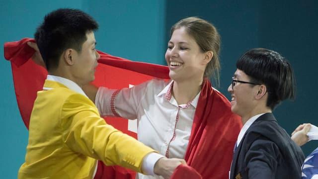 Ramona Bolliger mit Schweizerfahne umarmt andere Wettbewerbsteilnehmende