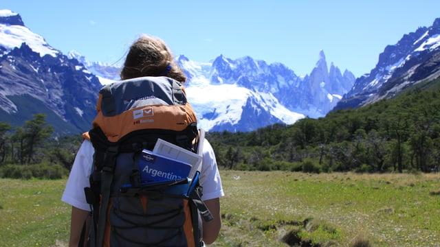 """Eine Frau vor Schneebergen. In ihrem Rucksack steckt ein Reiseführer mit der Aufschrift """"Argentina""""."""