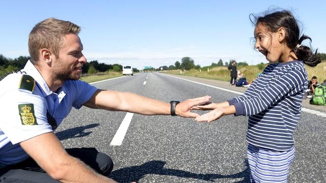 Ein Polizist kniend, ihm gegenüber ein herzhaft lachendes Mädchen, sie spielen ein Spiel mit den Händen.