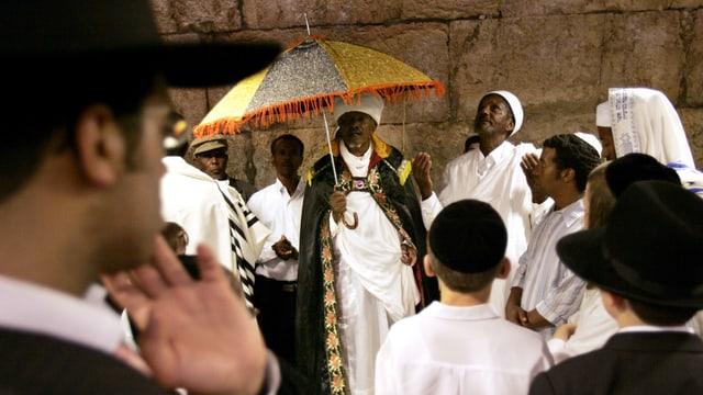 Orthodoxe Juden beobachten äthiopische Juden in weissen Kleidern, die vor einer Mauer stehen.