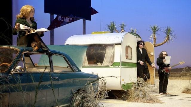 Ein Wohnwagen in der Wüste, davor zwei Musiker