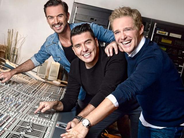 Drei Männer am Mischpult im Tonstudio.