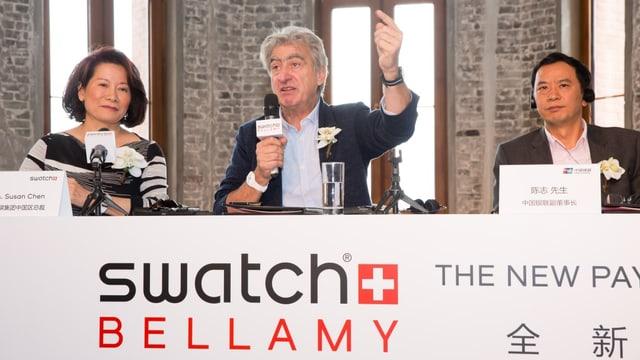 Der Swatch-CEO hebt eine Hand in die Höhe und mit der anderen Hand hält er ein Mikrofon.