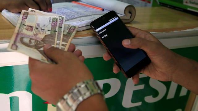Geldscheine in der einen Hand, ein Handy in der anderen.