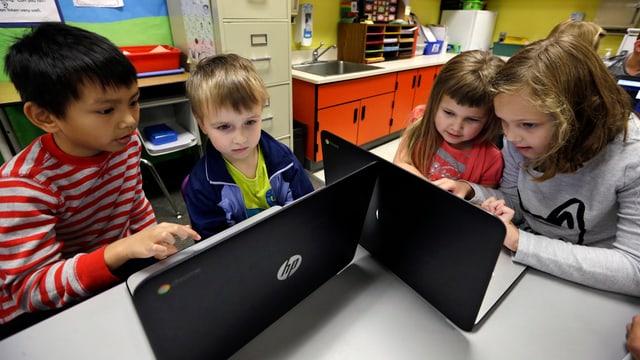 Vier Schulkinder sitzen an zwei Laptops