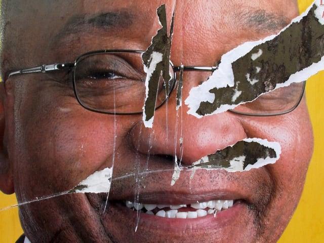 Zerkratztes Plakat mit dem Bild von Zuma.