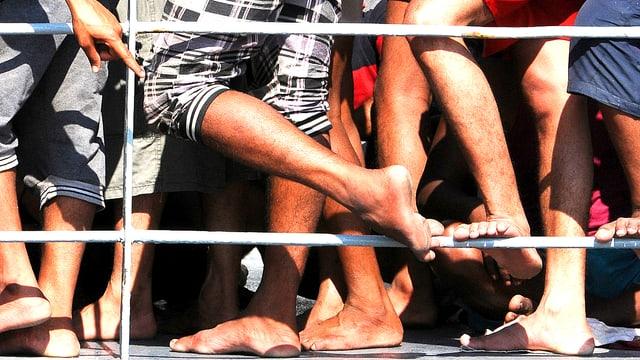 Ein Gewirr von Füssen und Beinen an der Reling eines Flüchtlingsschiffes, das in Lampedusa angekommen ist.
