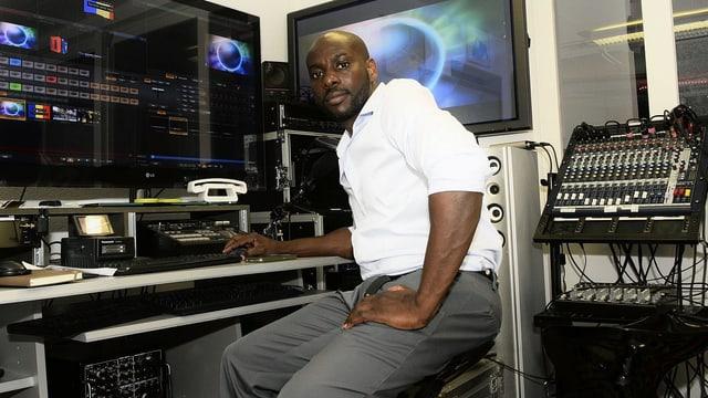 Ein Mann sitzt vor einem grossen Bildschirm.