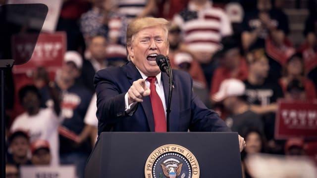 Trump spricht auf einem Podest und gestikuliert.