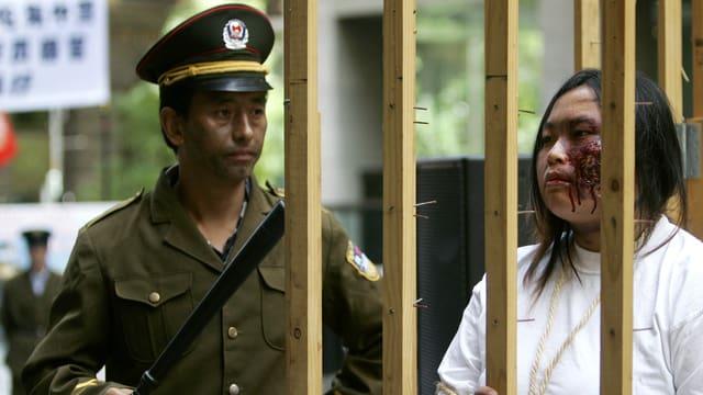 Falung-Gong-Anhänger in falscher Polizeiuniform (links) bewacht eine als Gefangene verkleidete Frau.