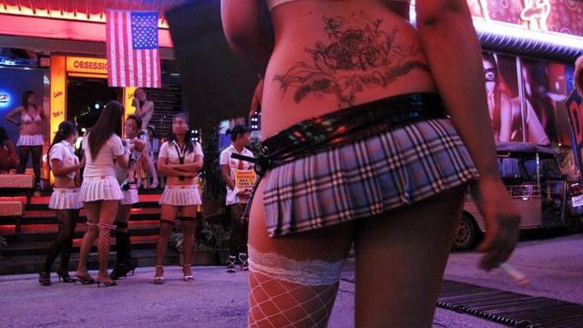 Junge Frauen stehen vor Bars herum.