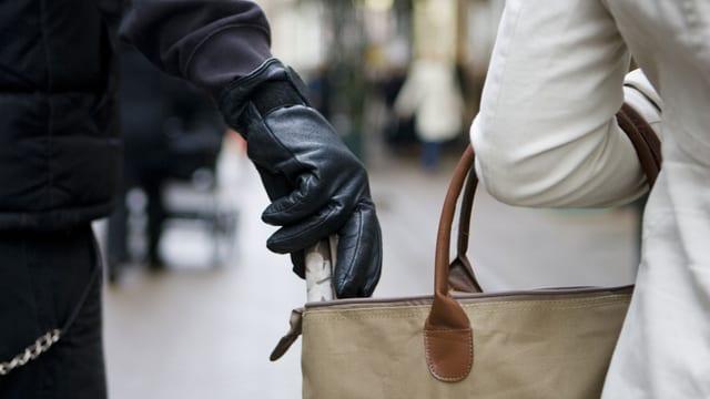Hand mit Handschuh greift in eine Damenhandtasche.