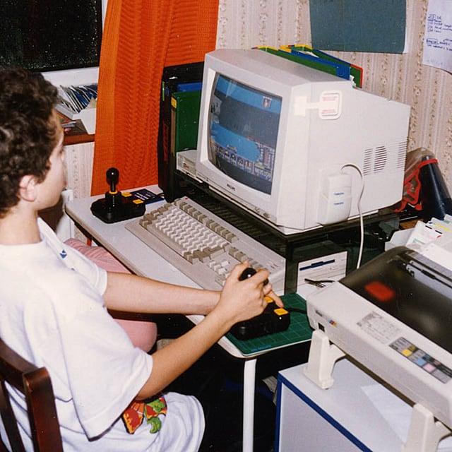 Ein Junge sitzt vor einer Amiga 500.