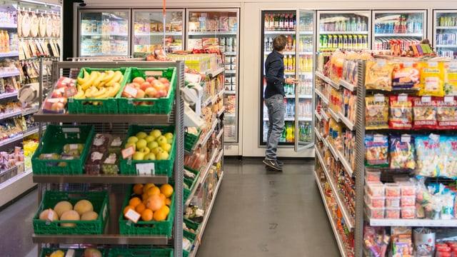 Ein Kunde nimmt sich in einem Convenience-Laden ein Produkt aus dem Kühlschrank.