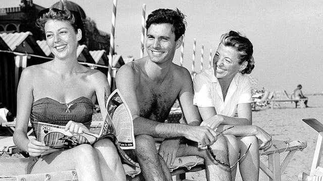 Jourdan sitzt lachend neben den beiden Frauen auf einem Liegestuhl am Strand.