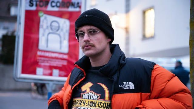 ein Mann sitzt mit Jacke, Kappe und Brille auf einer Bank