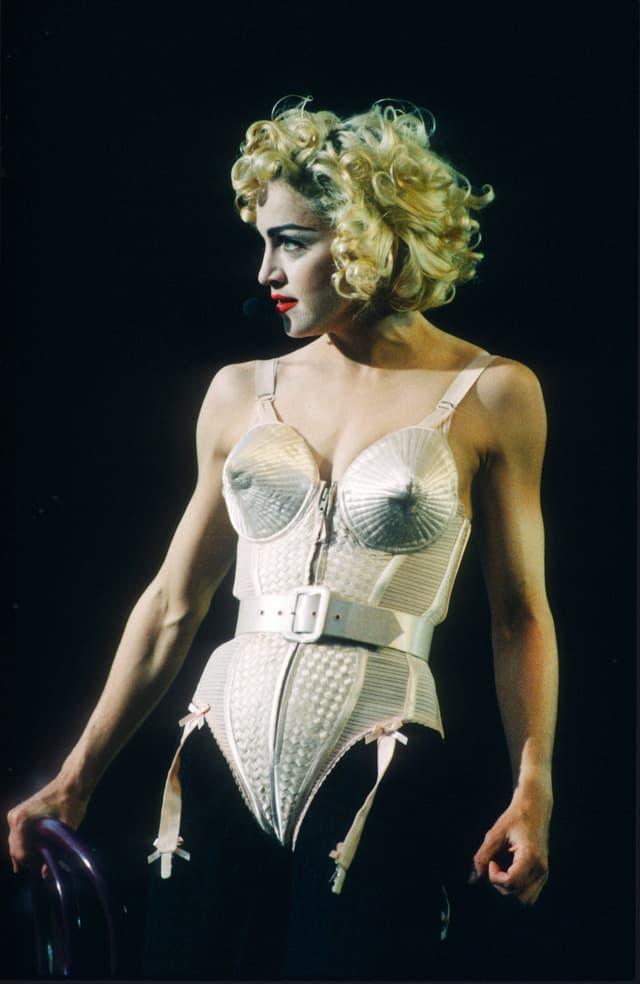 Eien Frau mit einem beigefarbenen Korsettt und blonden Locken steht auf der Bühne