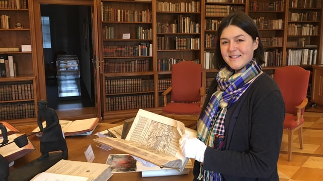 Bibliotheksleiterin Franziska Eggimann zeigt eines der ältesten Bücher der GF-Eisenbibliothek.