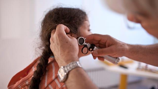 Arzt untersucht das Ohr eines Kindes