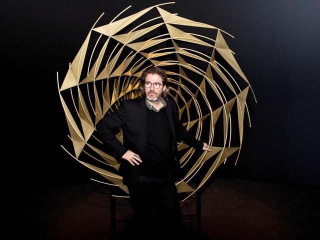 Olafur Eliasson steht vor einem goldenen Spirale.