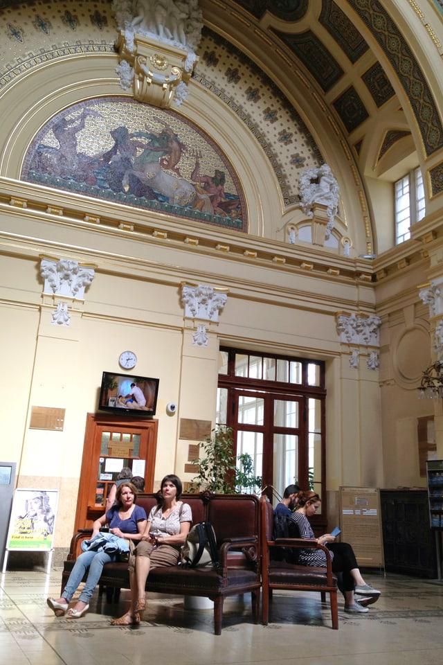 In einer geschmückten, hohen Eingangshalle sitzen ein paar Menschen auf Bänken.