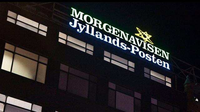 Das Firmenzeichen von Jyllands-Posten leuchtet über dem Büro in die Nacht.