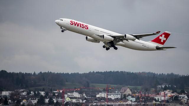 Startendes Passagierflugzeug über Häusern.