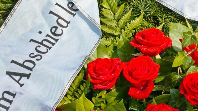 Ein Rosenkranz mit Schleife auf einem frischen Grab.