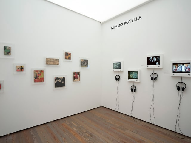 Der Blick in eine Ecke in den Museumsräumen: links ein paar Bilder, rechts kleine Bildschirme an der Wand.